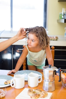 Mother's hand touching daughter's hair during breakfast