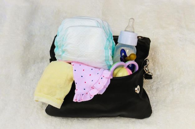 Mother's handbag with items to care for child on white. top view.