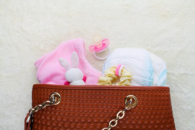 Mother's handbag with items to care for child on white