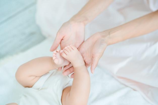 방에서 아기의 발을 지탱하는 어머니의 손