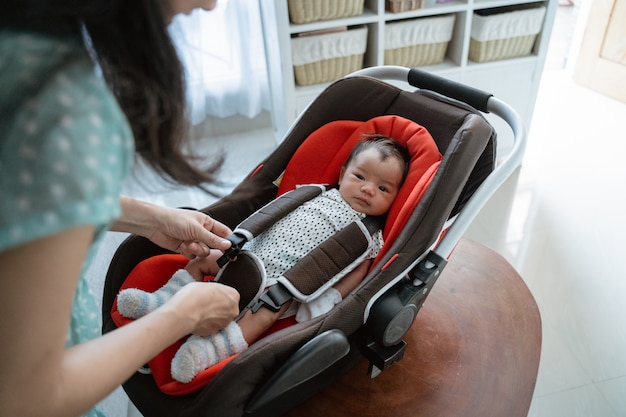 Mother's preparation puts the little girl in a baby seat