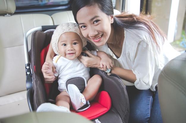 Мать обеспечивает своего ребенка в автокресле в ее машине