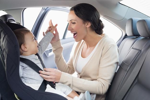 Мать, обеспечивающая ребенка на автокресле Premium Фотографии