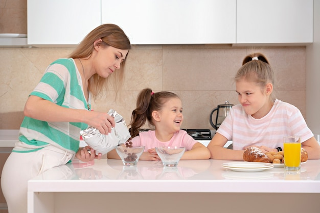 Mother serving breakfast to her two daughters at a table in kitchen, happy single mother concept