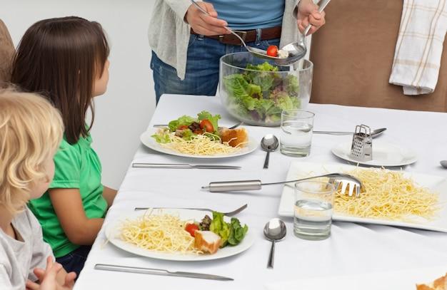 昼食時に子供たちにサラダを提供する母親