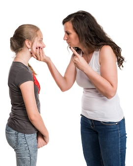 Mother shouting at her teenage daughter on a white wall