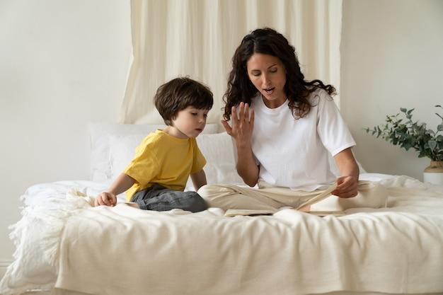 어머니는 책에 있는 이미지를 보여주고 유치원 교육을 돌보는 귀여운 미취학 아동에게 읽어줍니다.