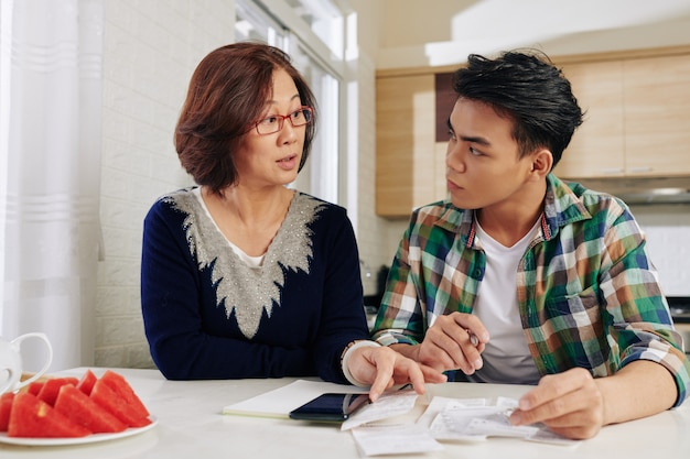 Mother showing bills to son