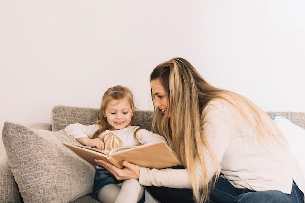 母親が娘に本を見せる