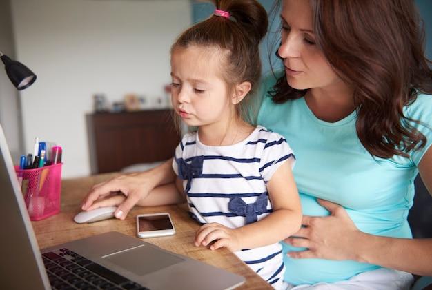 コンピューターの使い方を娘に示す母