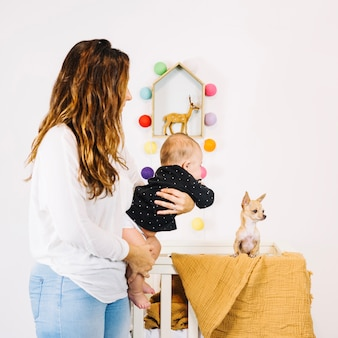 Mother showing dog to baby