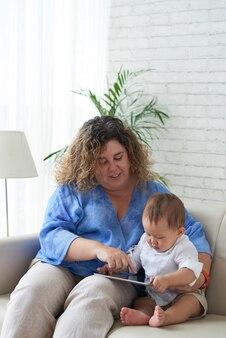 彼らがソファに座っているときに彼女の幼い息子にタブレットコンピュータで教育ビデオを見せている母親