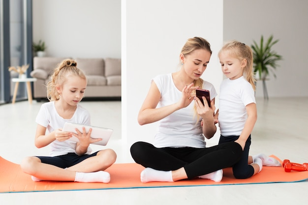 Mother showing something to daughters on smartphone while working out