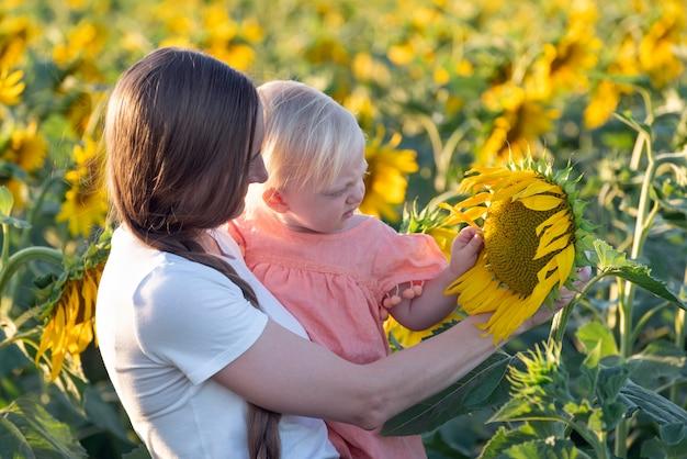 Мать показывает своей маленькой дочери большой цветок подсолнуха на поле