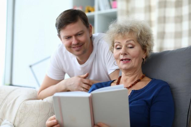 母はソファに座り、フォトアルバムを持ち、息子の写真を見せます。