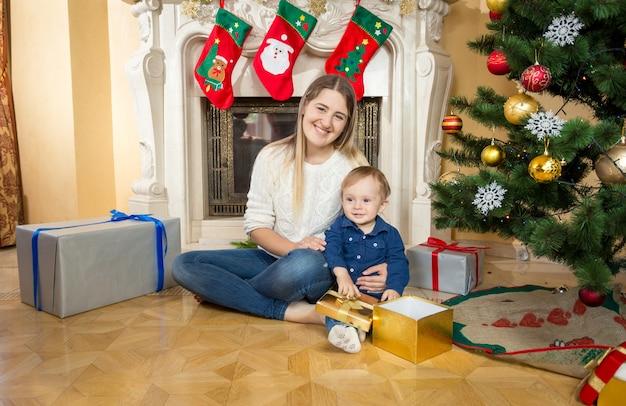 クリスマスのために飾られたリビングルームで赤ちゃんの息子と一緒に床に座っている母親
