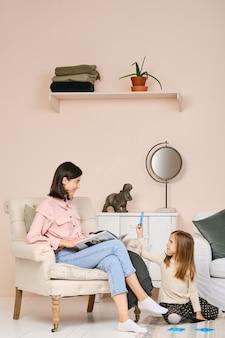 Мать сидит в кресле с книгой и смотрит на свою дочь, играющую на полу в гостиной