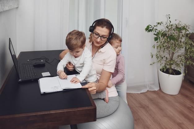 Мама сидит на фитнес-мяче в наушниках и работает дома с детьми во время карантина covid-19