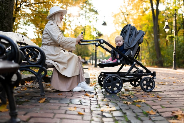 Мать сидит и качает ребенка в коляске