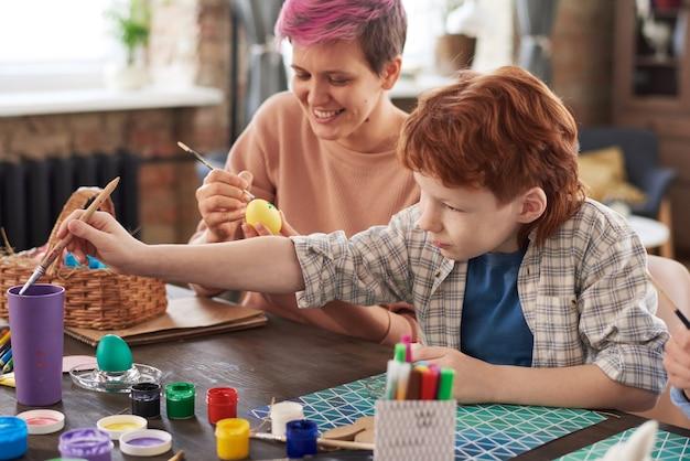 Мать сидит за столом и красит яйца вместе с сыном, они вместе готовятся к пасхе