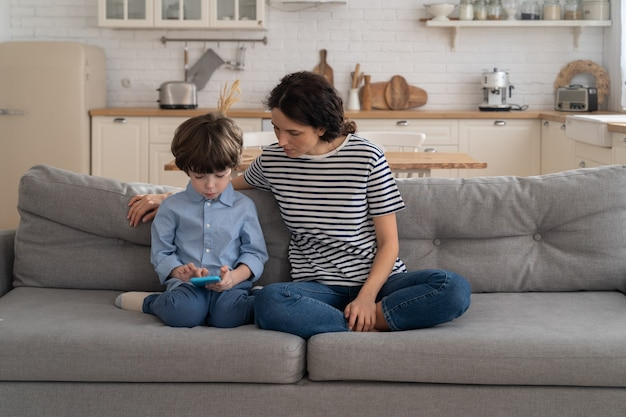 Mother sitting on couch with little kid watch cartoons, video on smartphone. happy loving family.