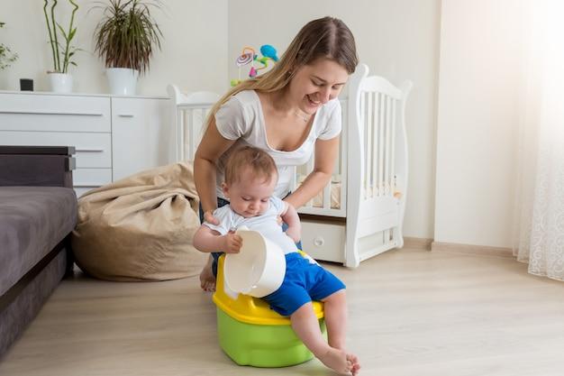 챔버 냄비에 그녀의 아기를 앉아 어머니