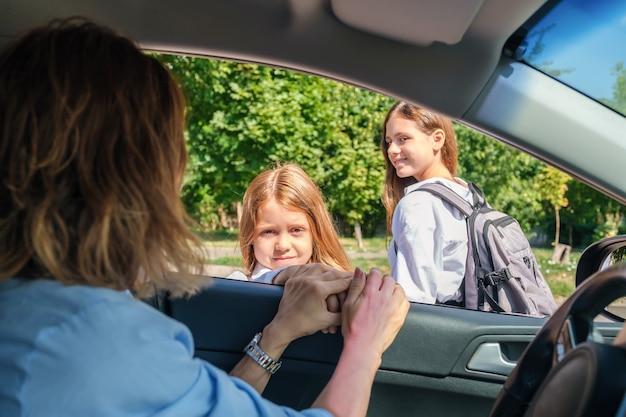 車の中に座って娘たちを学校に残している母親