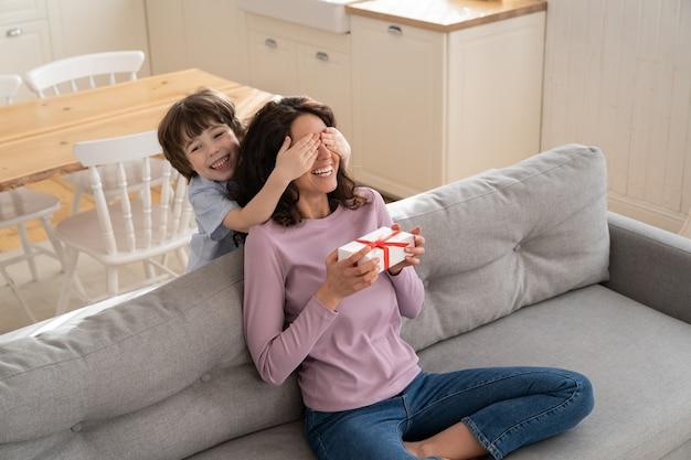 自宅のソファに座っている母親が母親の目を覆って祝福し、サプライズギフトを贈る