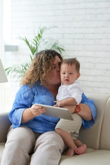 男の子と一緒に自宅のソファに座って、頬にキスをし、デジタルタブレットでアニメを見せている母親