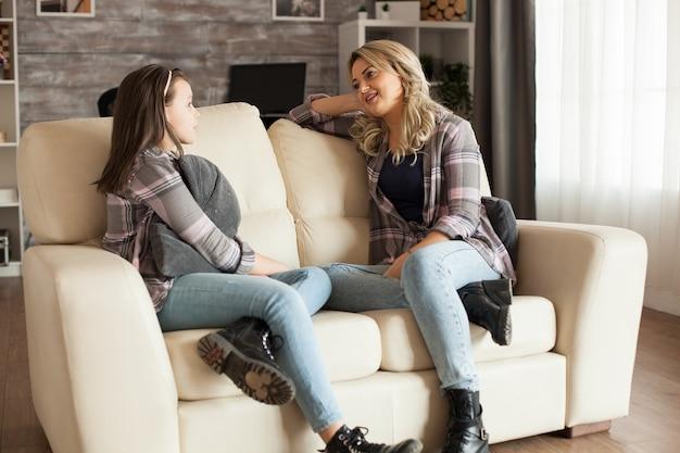 어머니는 거실에서 소파에 앉아 어린 딸과 이야기하고 있습니다. 부모의 사랑.