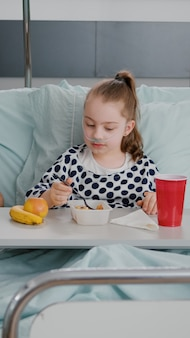 Mother sitting with sick child patient while eating healthy food lunch in hospital ward