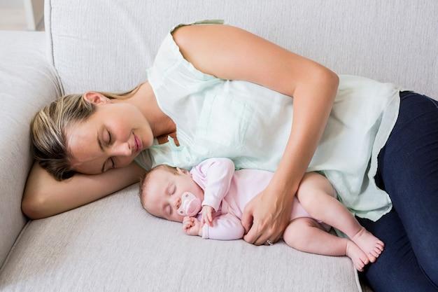 リビングルームで彼女の赤ちゃんと一緒に寝ている母