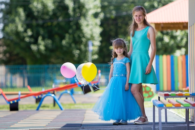 Mother and small daughter in blue evening dress.