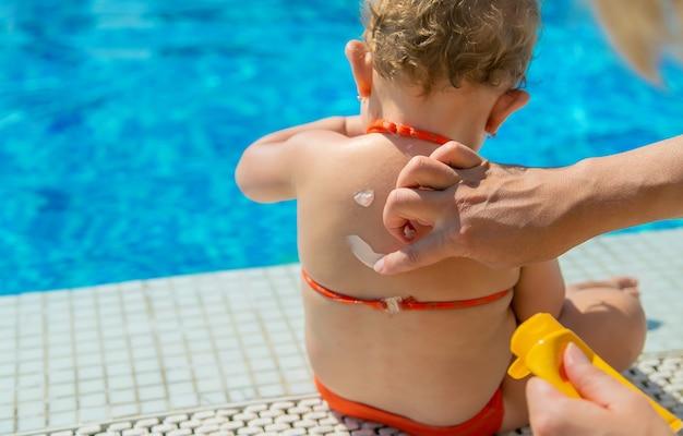 母親は子供の背中に日焼け止めを塗った。セレクティブフォーカス。赤ちゃん。