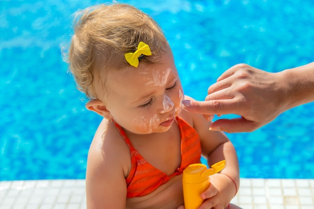 Mother smears sunscreen on the child face. selective focus. kid.