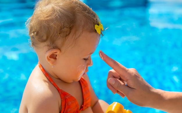 母は子供の顔に日焼け止めを塗ります。セレクティブフォーカス。子供。
