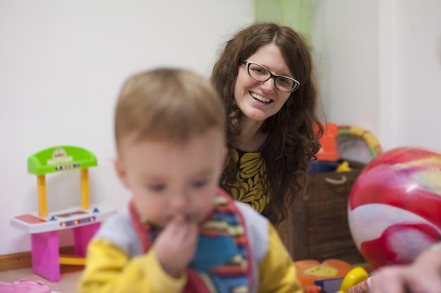 어머니는 조기 자극 세션 동안 아이가 노는 모습을 보고 미소를 짓습니다.