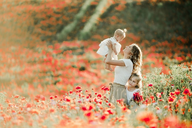 Mother smiles to her baby, elder daughter nestles to mom on the poppy field