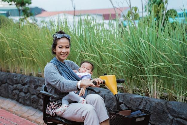 バギー車を運転している間、母親は赤ちゃんを抱いて微笑む