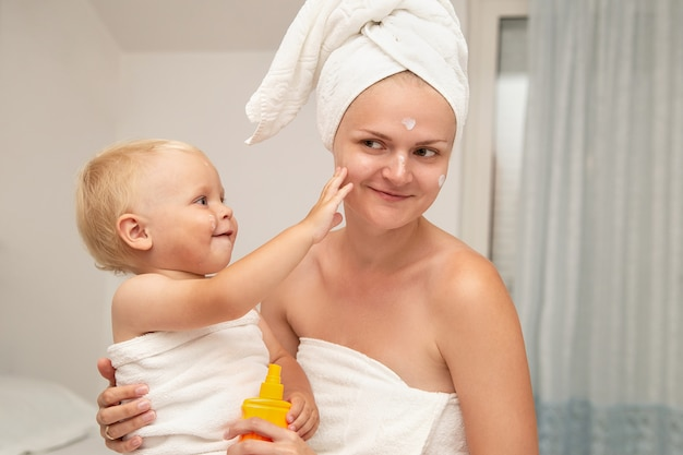 Mother and smiley infant baby in white towels after bathing apply sunscreen or after sun lotion