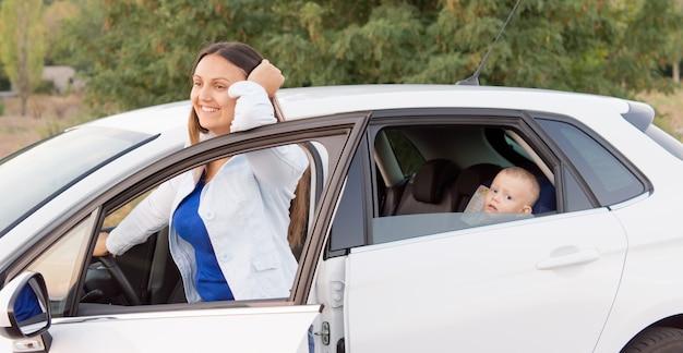 幼い息子が車の後ろから見ている間、彼女は彼女の車の横にある開いたドアの外に立っているので、期待して微笑んでいる母親