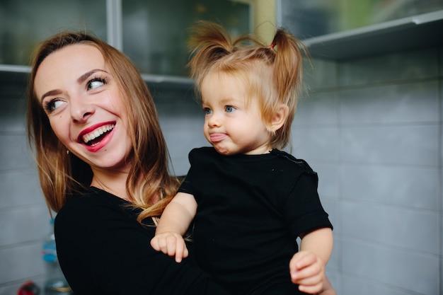 어머니는 팔에 딸과 함께 웃고 혀로 소녀