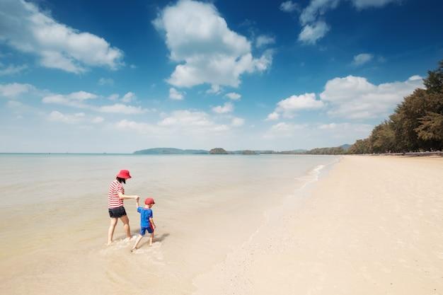 Una madre e figlio sulla spiaggia all'aperto mare e cielo blu