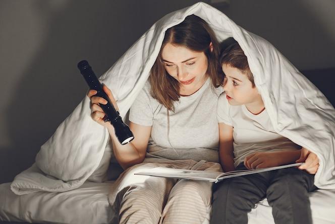 Madre e figlio sotto la coperta a letto leggendo un libro.