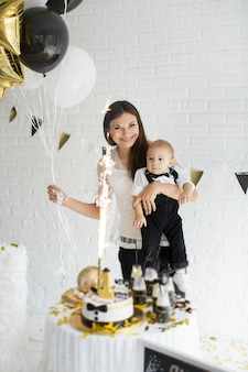 Mother and son celebrating the 1st birthday together laughing and smiling with balloons, a candy bar.