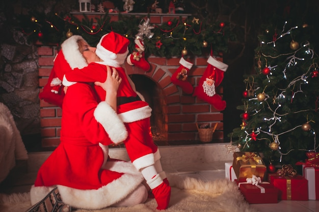 Mother and son in christmas room with decorated tree and fireplace