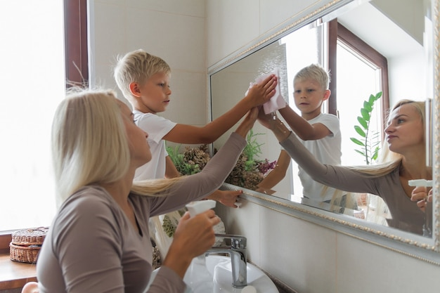 Mother and son do cleaning together and clean the bathroom mirror