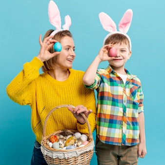 Mother and son covering eyes with painted egg