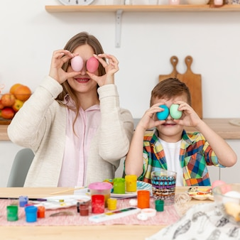 Mother and son covering eyes with painted eggs
