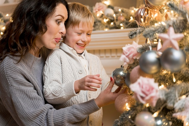 Mother and son decorating the christmas tree